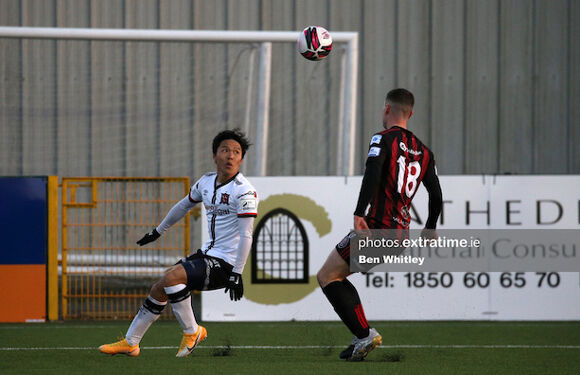 Han Jeongwoo and James Finnerty compete for the ball in Oriel Park