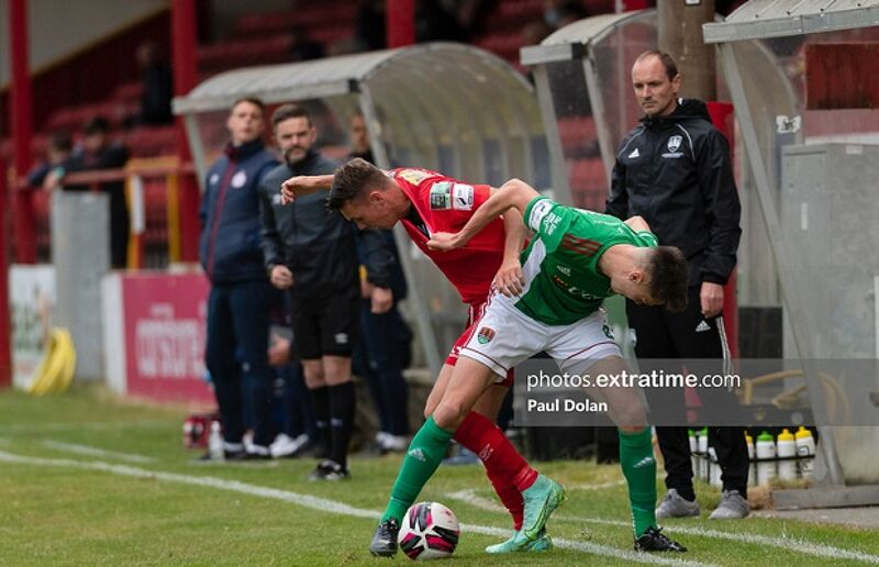 Cork City boss Colin Healy watches on as City's Cian Coleman tussles for possession against Dayle Rooney of Shelbourne